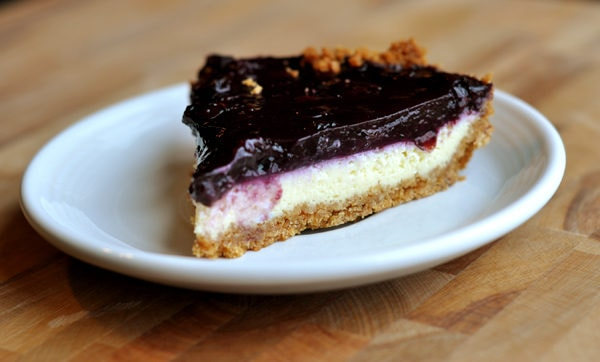 slice of cheesecake with blueberry topping on a white plate