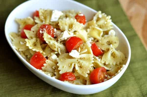 white bowl full of cooked bowtie pasta, sliced cherry tomatoes, and feta