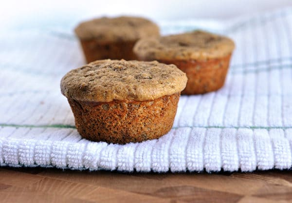Three cooked bran muffins on a kitchen towel.