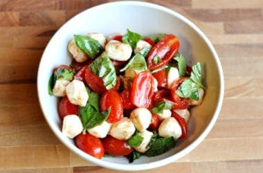top view of a white bowl with sliced tomatoes, mozzarella balls, and spinach drizzled in oil