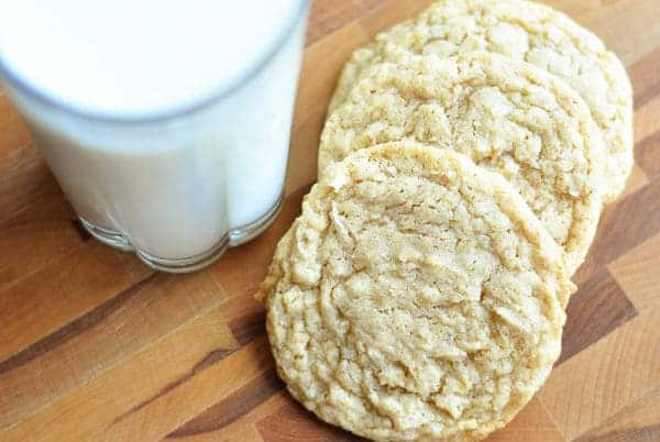 light brown cookies next to a glass of milk