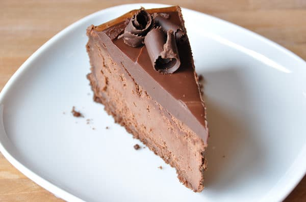 a thick slice of chocolate cheesecake with chocolate curls on top on a white plate