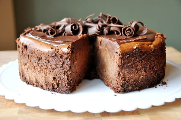 a thick chocolate cheesecake with chocolate curls on top and one slice of cheesecake cut out