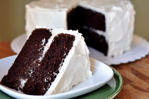 a big slice of two-tiered chocolate cake with white frosting on a white plate, with the rest of the cake behind it