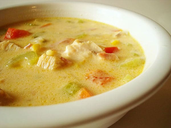 chicken chowder with corn and chopped peppers in a white bowl