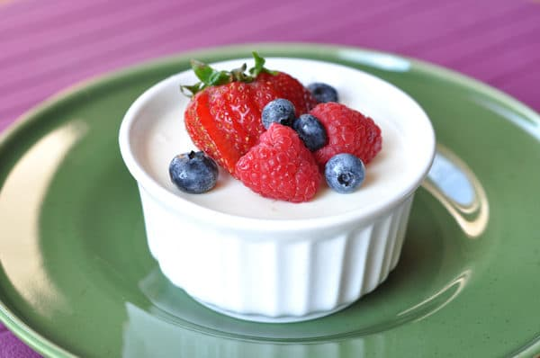 small white ramekin filled with cream and topped with fresh berries