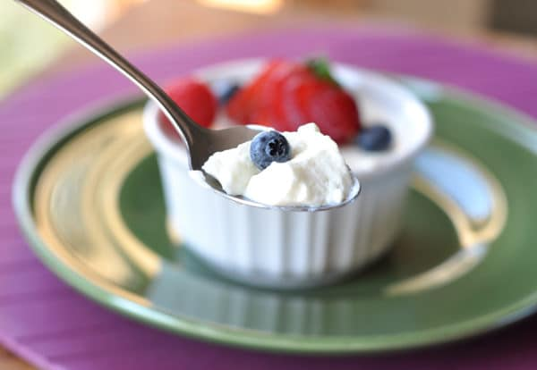 small white ramekin with cream dessert topped with fresh berries, and a spoon taking a bite out
