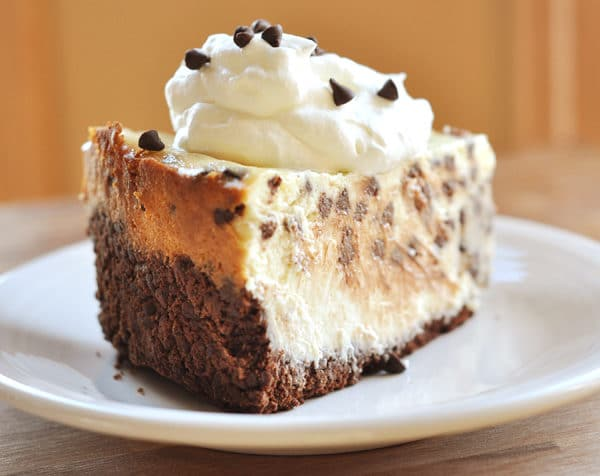 back view of a chocolate studded slice of cheesecake topped with whipped cream and chocolate chips