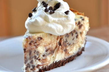 chocolate chip studded cheesecake with chocolate crust and topped with whipped cream and mini chocolate chips