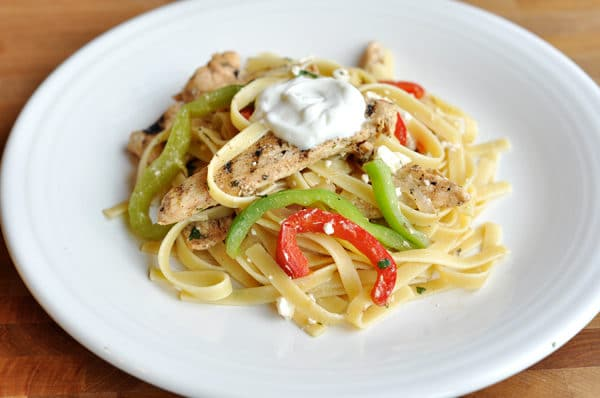 cooked pasta, bell pepper slices, and grilled chicken on a white plate