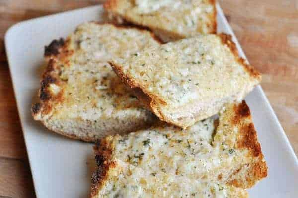 slices of baked garlic bread on a white plate