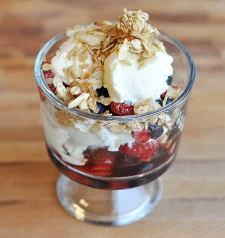 berry, yogurt, and granola parfait in a glass goblet