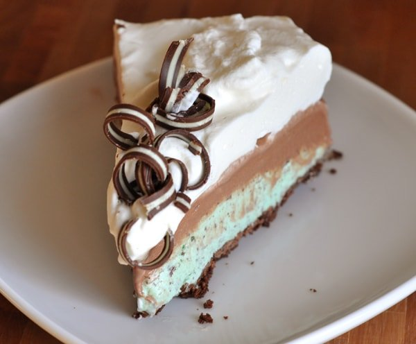 a slice of pie with a mint ice cream base, chocolate middle, and whipped cream and chocolate curls on top.