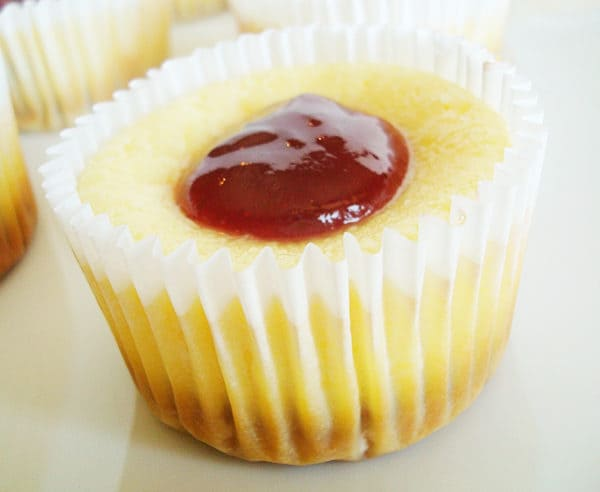cheesecake in white muffin liner with dollop of raspberry in center