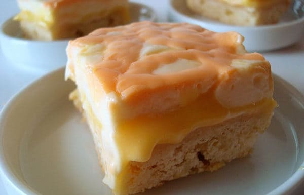 bar with shortbread crust, orange curd middle, and cream top on a white plate
