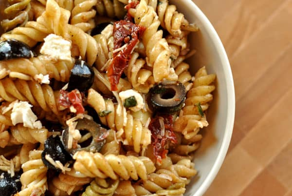 white bowl filled with cooked rotini, sliced olives, and sun-dried tomatoes