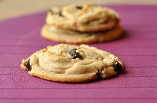 a chocolate chip cookie on a purple table, with two more cookies in the background