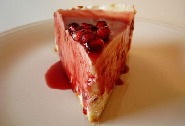 slice of cheesecake with pomegranate sauce on top