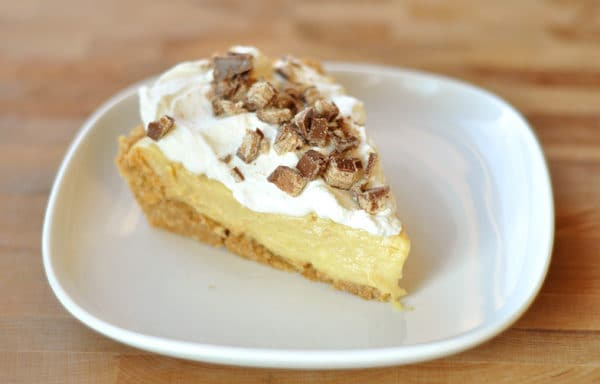 slice of pudding pie with graham cracker crust, pudding layer, and whipped cream and toffee bits on top