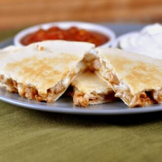 triangle pieces of cooked chicken quesadilla on a gray plate