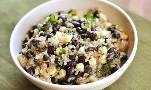 looking down at a white bowl with quinoa, corn, and black beans
