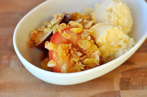 a white bowl of roasted fruit with a crunchy topping and vanilla ice cream