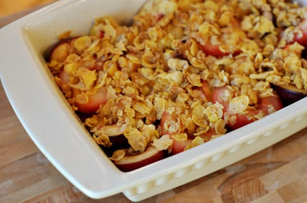 white casserole dish with roasted fruit and a crunchy topping