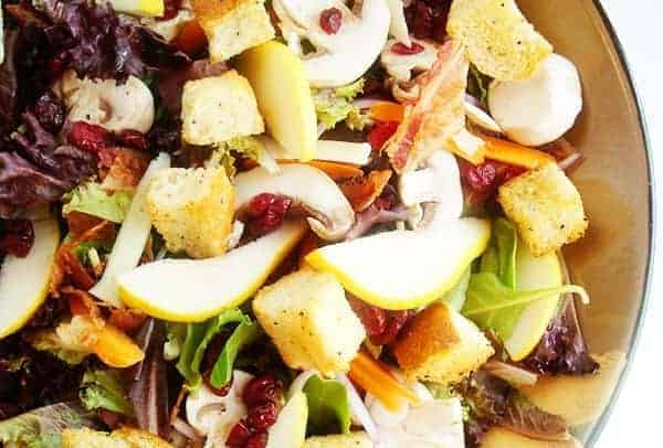 greens, sliced pear, and croutons in a bowl