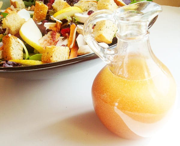 small glass pitcher of salad dressing next to a bowl of salad