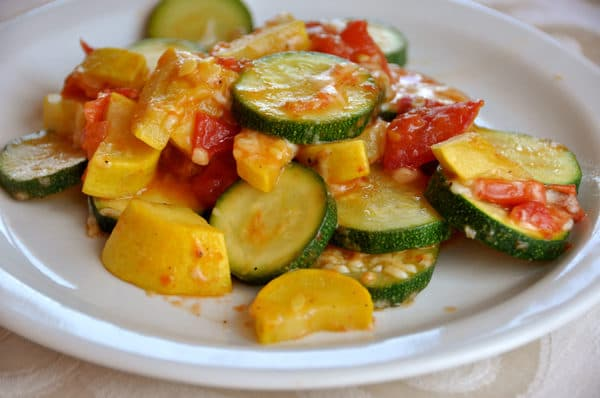 white plate tomatoes, and cooked zucchini and squash