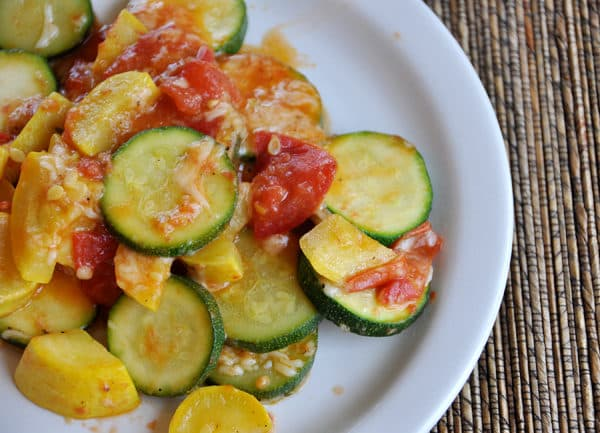 white plate of sauteed zucchini and yellow squash slices, with a tomato sauce on top