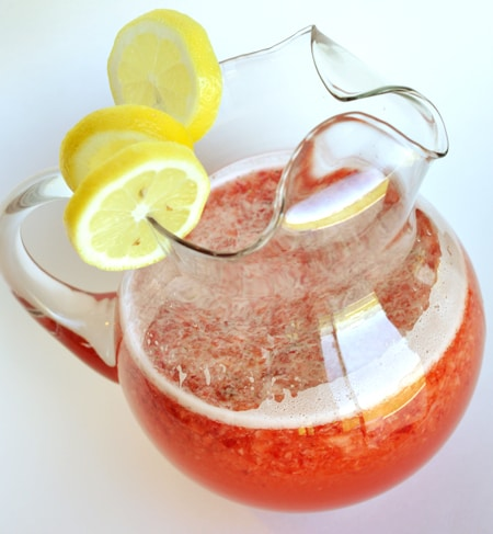 glass pitcher with lemon slices on top and half full of strawberry lemonade