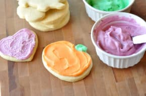 frosted heart and pumpkin sugar cookies, with ramekins of pink and green frosting and a stack of unfrosted sugar cookies all on a brown table