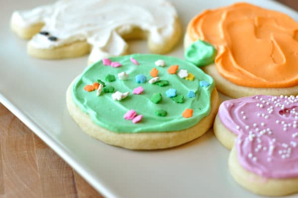 frosted pumpkin, apple, heart, and ghost sugar cookies on a white platter