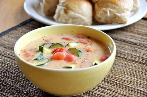 bowl of soup filled with zucchini and tomatoes with a plate of rolls behind it