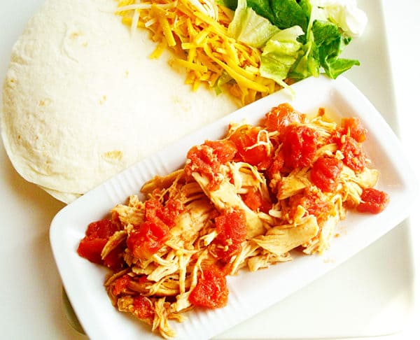 shredded chicken and tomatoes in a white platter with white tortillas on the side