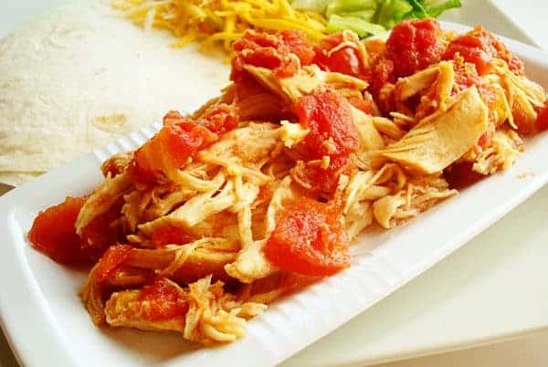 white rectangular platter with shredded chicken and diced tomatoes