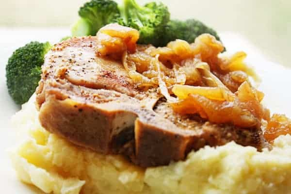 cooked bone-in pork chop on top of mashed potatoes