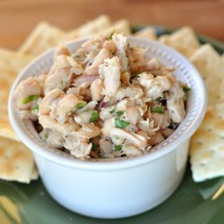 white ramekin of white bean tuna salad on a green plate with crackers surrounding the salad