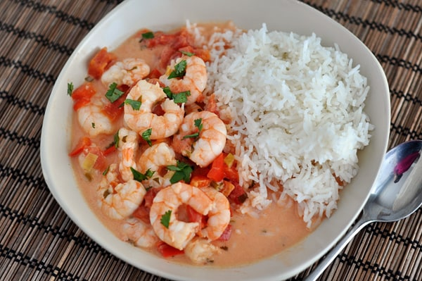 top view of cooked shrimp bathed in a tomato sauce mixture with cooked white rice on the side