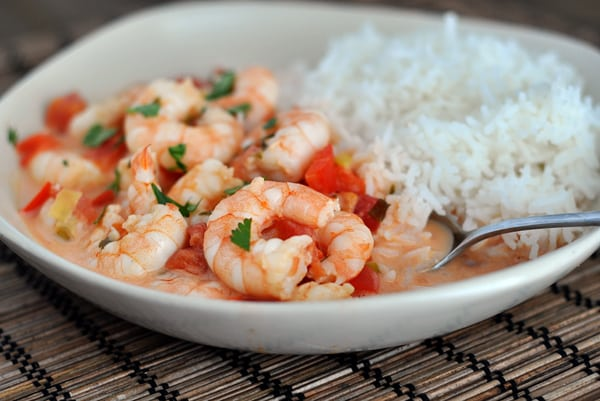 a white bowl with shrimp and tomato sauce on one side and cooked white rice on the other