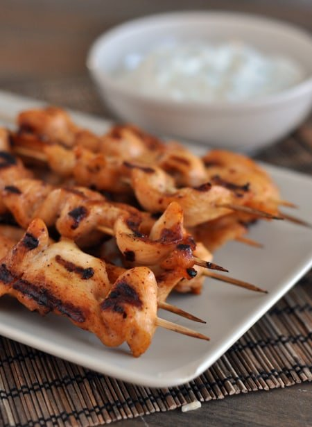 white platter with grilled chicken skewers with a bowl of dipping sauce behind it