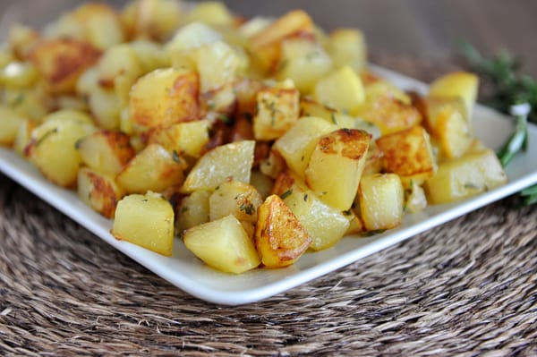 golden brown cooked potato cubes on a white platter