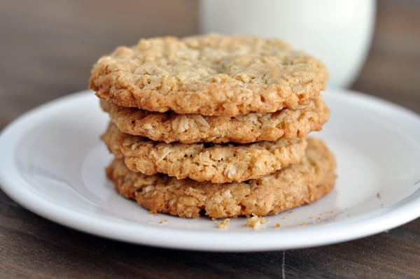 four thin and crispy oatmeal cookies stacked on top of each other on a white plate
