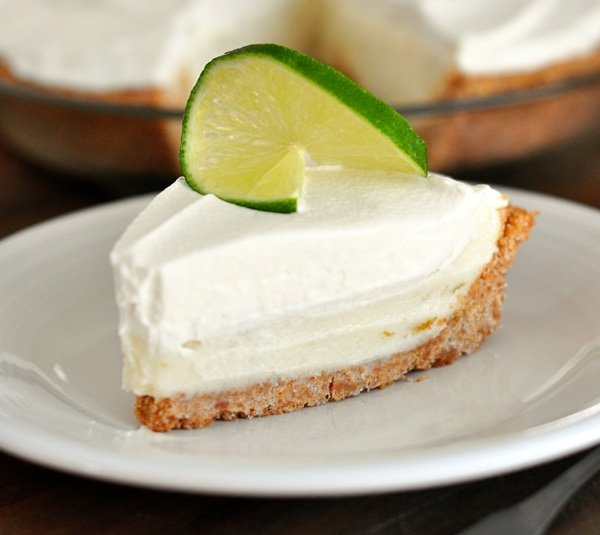 a slice of sour cream lime tart on a white plate, with a slice of lime on top