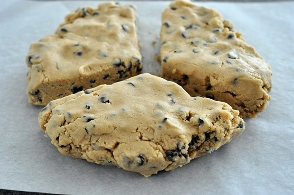 three chunks of chocolate chip cookie dough on a piece of parchment