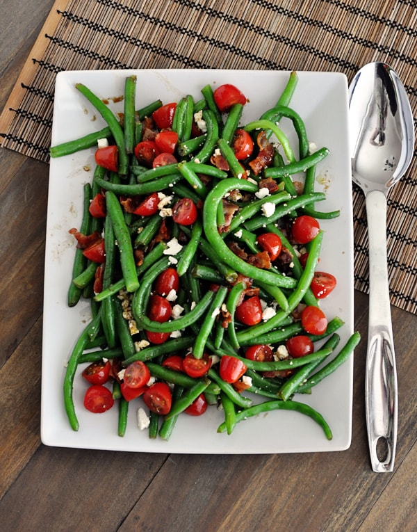 A top view of a white platter full of green beans, sliced cherry tomatoes, feta, and bacon sprinkled throughout.