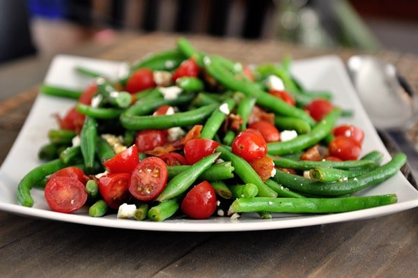A white platter with cooked green beans, sliced cherry tomatoes, and feta cheese sprinkled throughout.