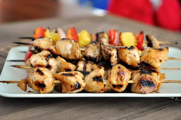 white platter with grilled chicken kebabs and veggie kebabs
