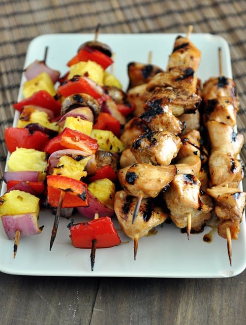 top view of a white platter with grilled chicken and veggie kebabs